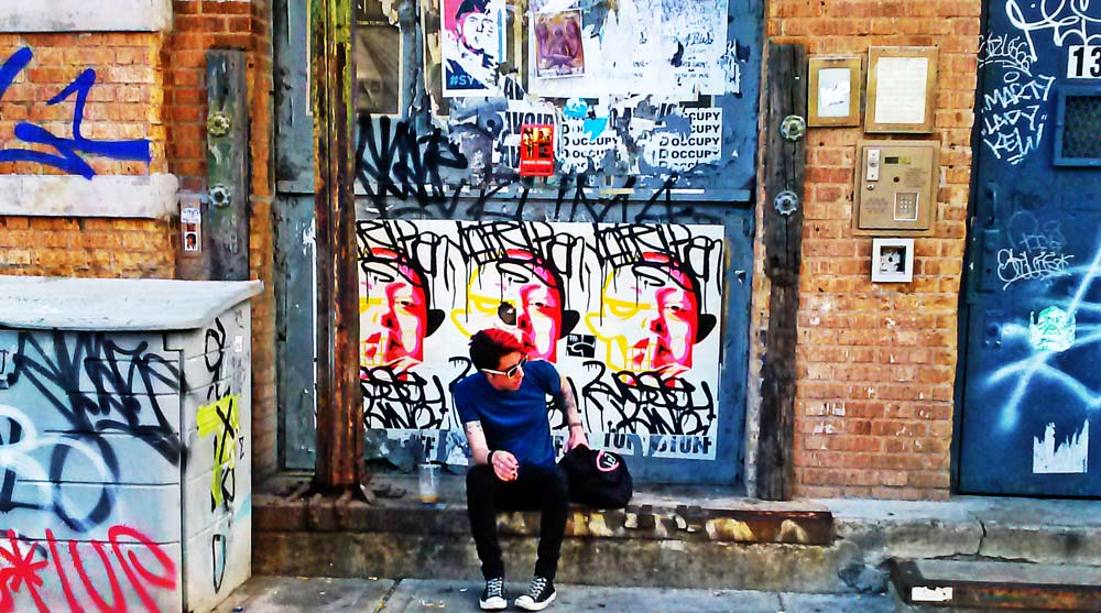 Hipster sitting in front of building covered in graffiti in Williamsburg, Brooklyn.