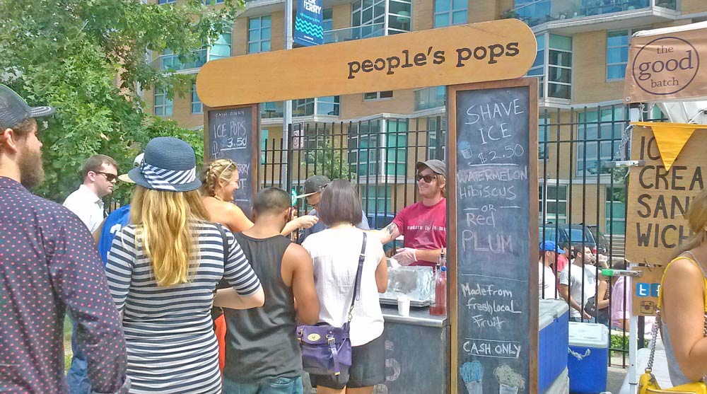 Group of people standing in line for ice pop vendor at Brooklyn outdoor market.