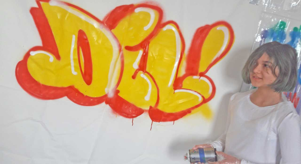 Young girl hold spray paint can and posing with graffiti lettering.