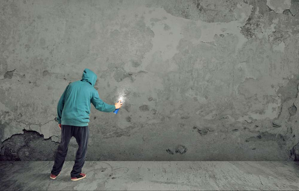 Hooded man spray painting on blank wall