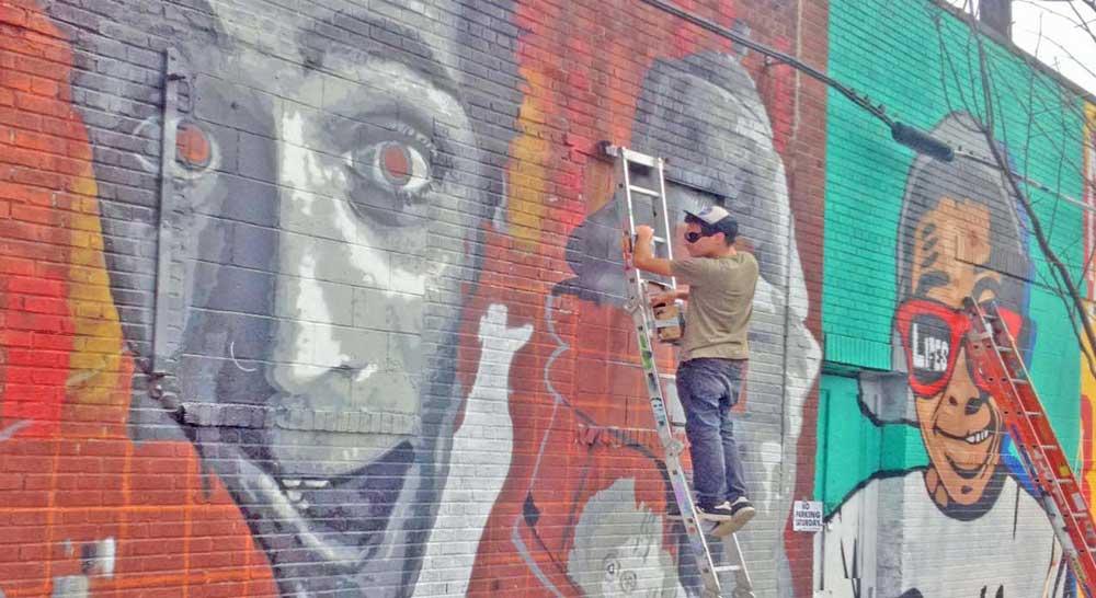 Street artist spray painting graffiti artwork.