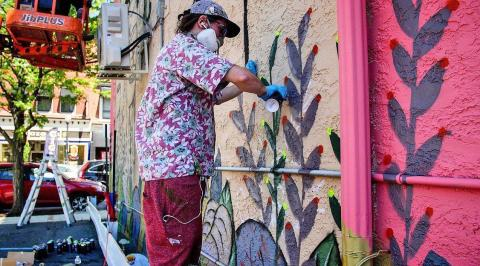 Street artist painting on wall.