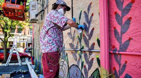 Street artist painting on wall.