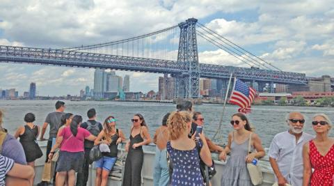 People standing on deck of ferry boat with Brooklyn in the background.