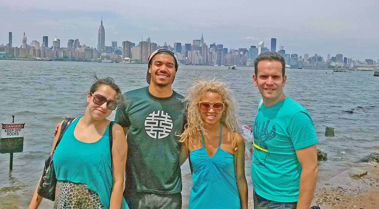 Young people posing with New York City skyline behind them.